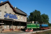 Rosnička smodrým výletním vozem předstaniční budovou stanice Třemešná veSlezsku