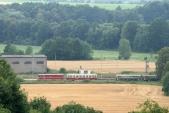 Fotografie pořízená z polské obce Stara Wies zabírá Osoblažské nádraží s odjíždějícím vlakem ČD v čele s lokomotivou 705 913, 10.8.2013