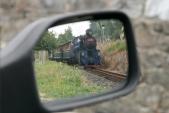 Parní lokomotivu U57.001 vidí ve svém zpětném zrcátku řidič automobilu stojícího na přejezdu u nádraží v Třemešné, 10.8.2013