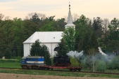 Transport lokomotivy U46.002 vedený lokomotivou 720 039 projíždí okolo linhartovského kostela.