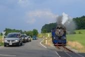 Světelný přejezd se silnicí I/57 u Třemešné se sjíždějícím parním vlakem SZD.