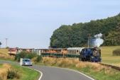Souprava parního vlaku sjíždí k přejezdu se silnicí I/57