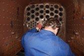 Práce na parní lokomotivě mohou být pěkně stísněné. Zde se třeba vidíme kolegu sedícího v topeništi a dodělávajícího zařízení v popelníku.
